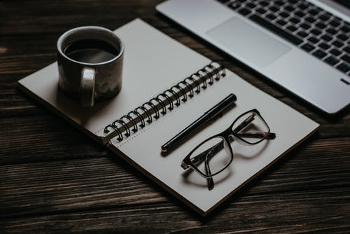 A Notebook with a Cup of Coffee and an Eyeglass on Top