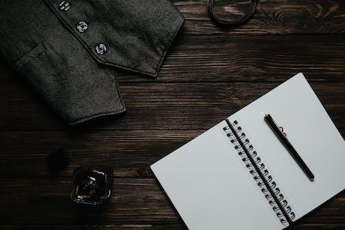 A Black Denin Vest Beside a Perfume Bottle and a Notebook