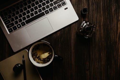 Macbook Pro Prateado Ao Lado Da Caneca De Cerâmica Preta Na Mesa De Madeira Marrom