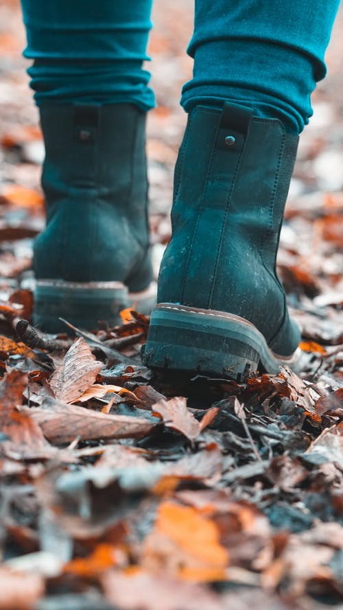 Person in Blue Denim Jeans and Black Boots Standing on Dry Leaves