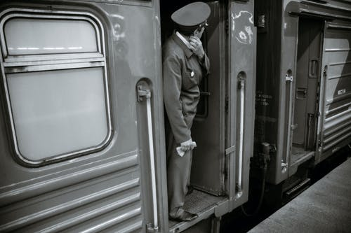 Anonymous male train steward waiting for departure
