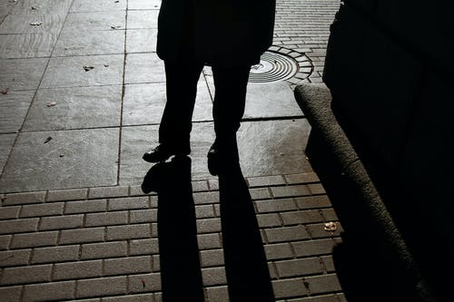 High angle silhouette of crop anonymous male in elegant coat standing on paved city street in evening