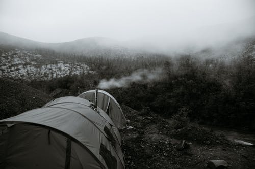 Camping tents in mountainous valley near forest on misty day