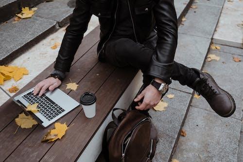 使用macbook Pro的黑色皮夾克的人