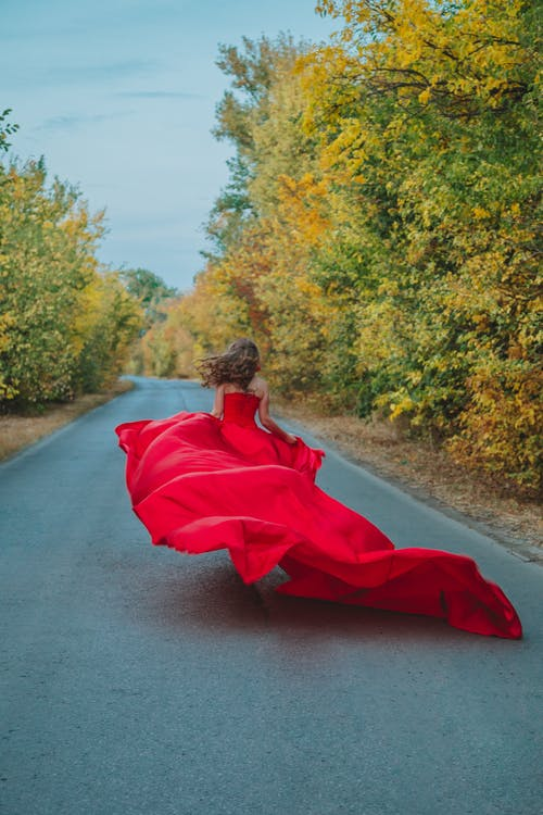 Back view of unrecognizable female in flowing long red dress running on asphalt road between autumn trees in countryside