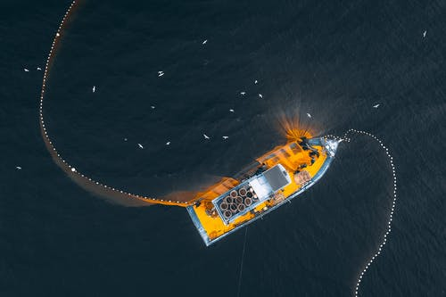 Aerial top view of modern fishing vessel with nets floating on dark seawater in daylight