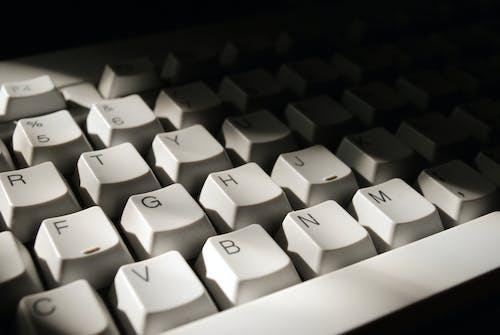 White Computer Keyboard on Black Surface