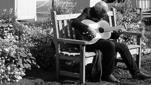 Grayscale Photo of Man Playing Guitar on Bench