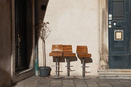 Wooden vintage chairs placed on pavement in street near potted dry plant and building doors with stone walls in sunny summer day in town