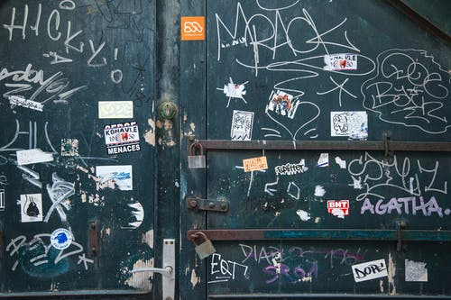 Weathered metal door with locks and doorhandle near white painted graffiti and small stickers in daylight