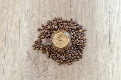 Flat Lay Photography of Mug Surrounded by Coffee Beans