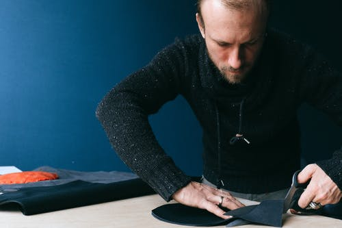 Concentrated male tailor with scissors cutting round shaped piece of leather while working with fabric in atelier