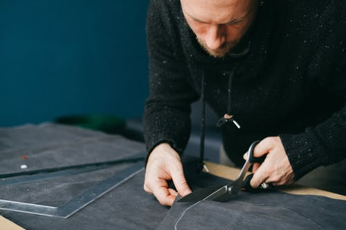 Serious male tailor with scissors cutting circle out of leather material while standing at workbench in atelier