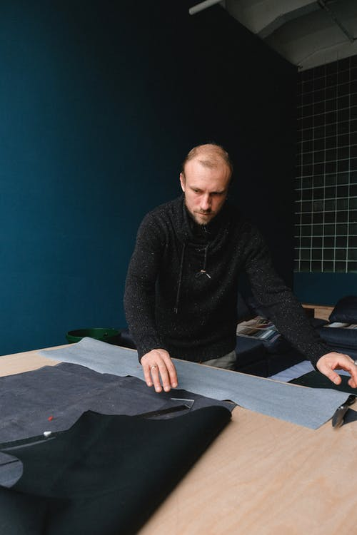 Focused male designer working with fabric in atelier