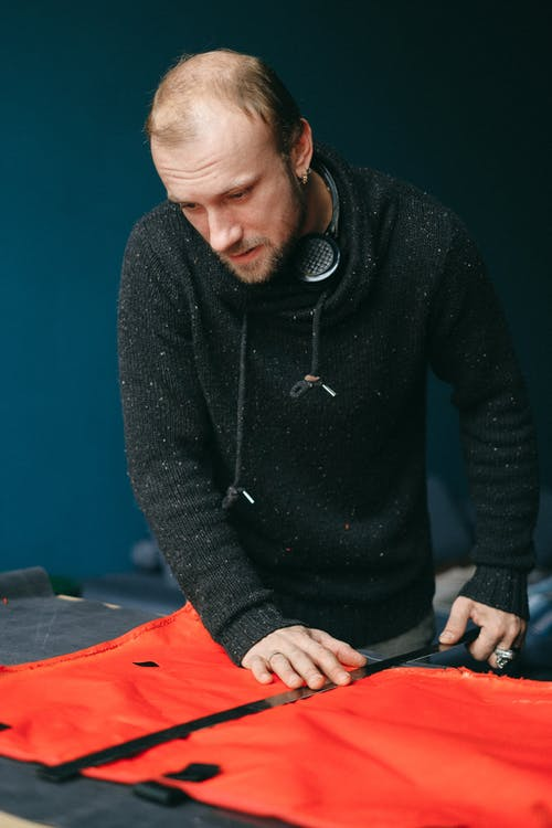 Focused male tailor working with piece of cloth in workshop