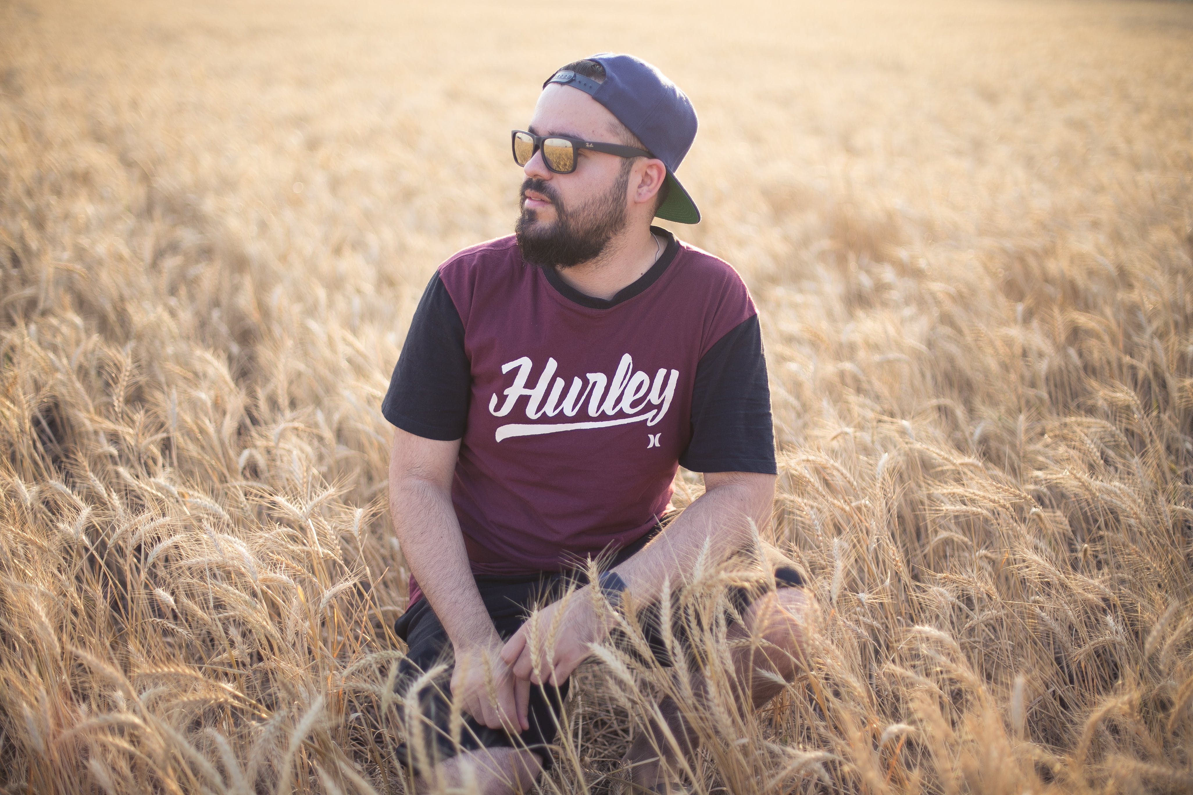 Selective Focus Photography of Man in Crouch Position on Wheat Field