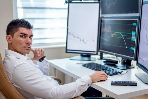 Man in White Long Sleeves Shirt Sitting in Front of a Computer