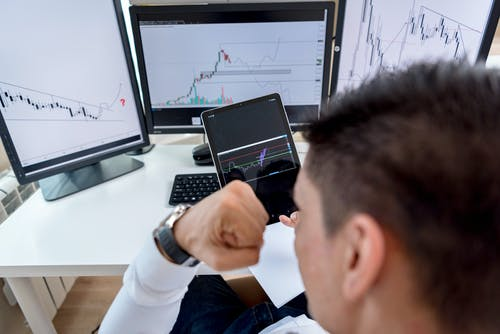 Man Monitoring Graphs on Multiple Screens