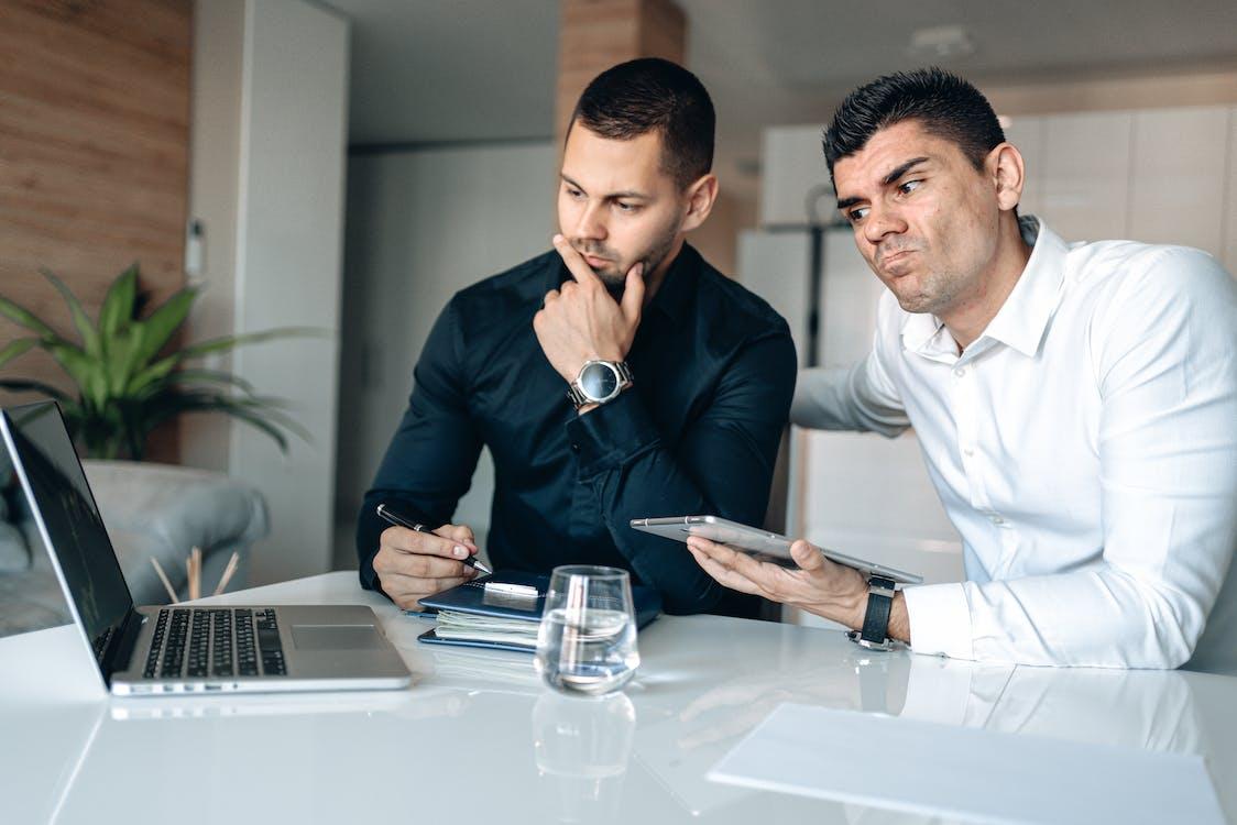 Man in Black Blazer Sitting Beside Man in White Dress Shirt