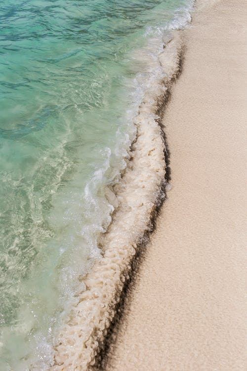 Tropical sea with sandy shore in sunlight