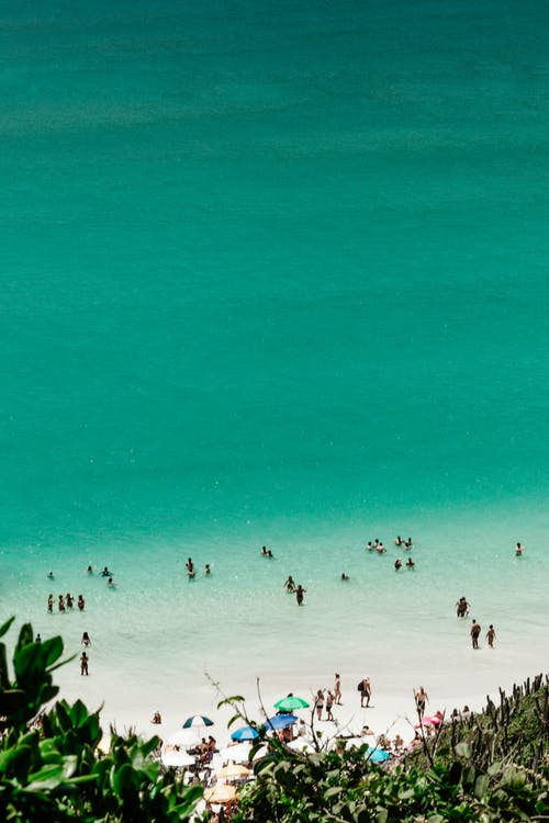 From above of distant unrecognizable tourists swimming in turquoise water of peaceful ocean with sandy beach on sunny day