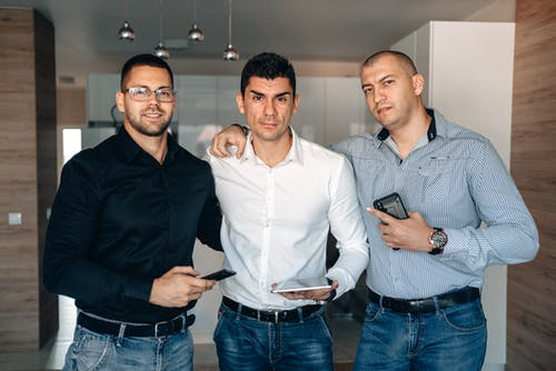 Men in Long Sleeve Shirts Holding Gadgets