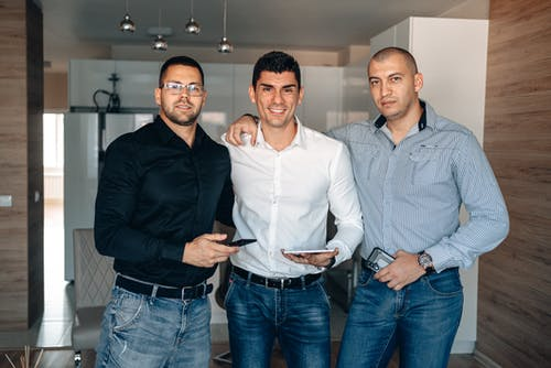 Three Men in Long Sleeve Shirt Standing Together Holding Gadgets