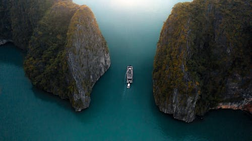 White Boat on Body of Water Near Mountain