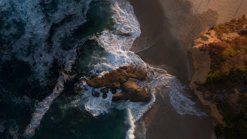 Water Waves Hitting Brown Rock