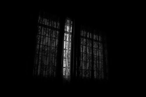 Black and white of dark room with closed drapes with creative ornaments and patterns hanging on window at home in darkness