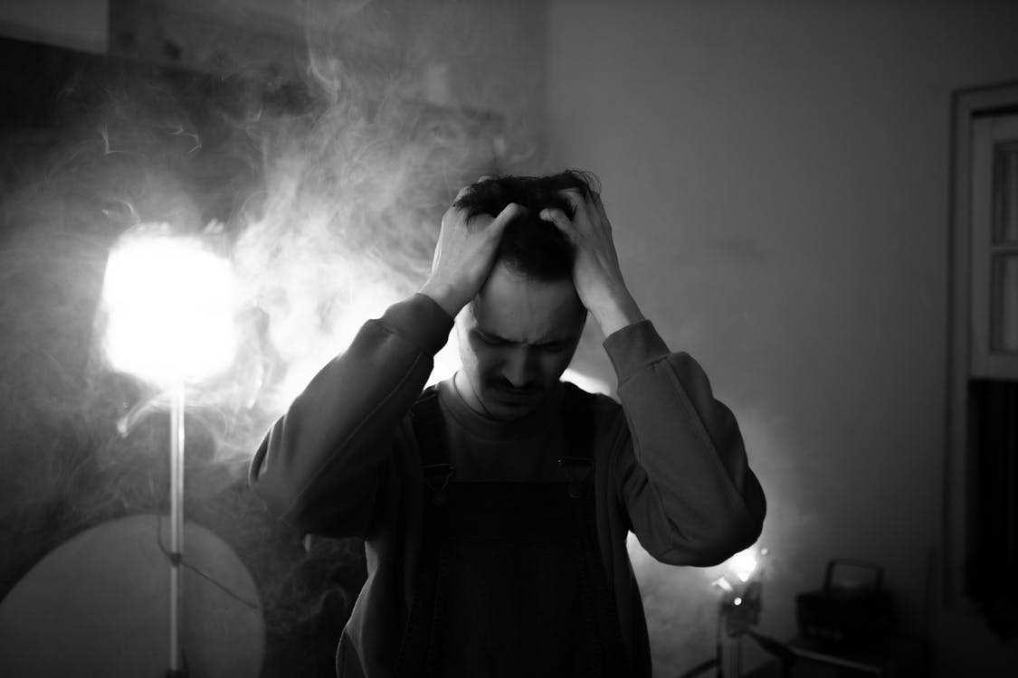 Black and white of upset male standing in room with lightning equipment and smoke while thinking about difficult decision at home
