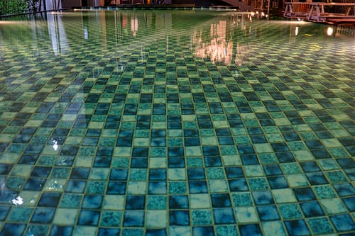 Swimming pool with blue tiles under constructions reflecting in shiny transparent aqua in daytime