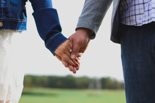 Crop couple holding hands in nature