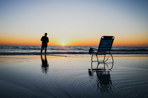 Back view of anonymous male standing on wet beach with chair and fishing against sky in sundown