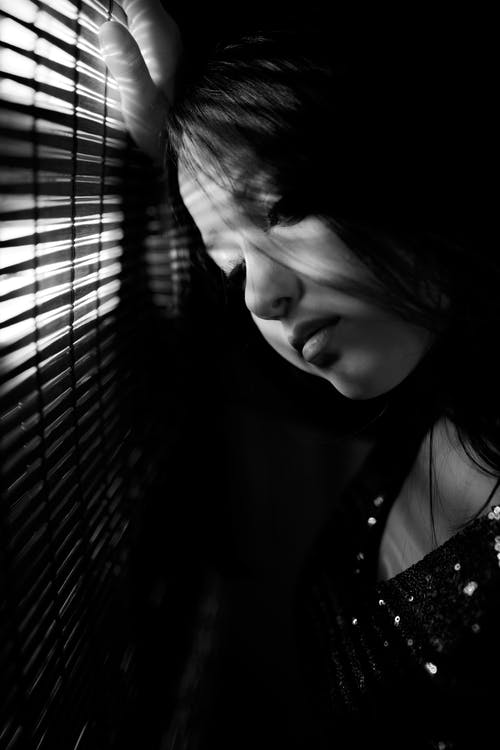 Black and white of young unhappy female with dark hair standing near window with jalousie in dark room at home