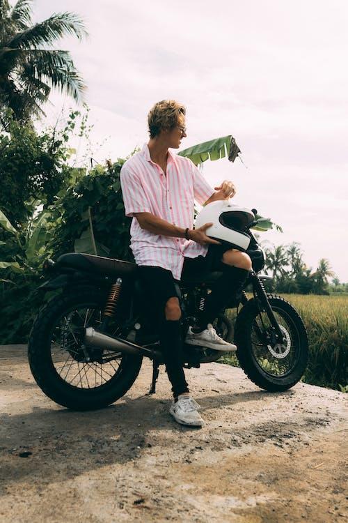 Man in Pink Dress Shirt Riding Black Motorcycle