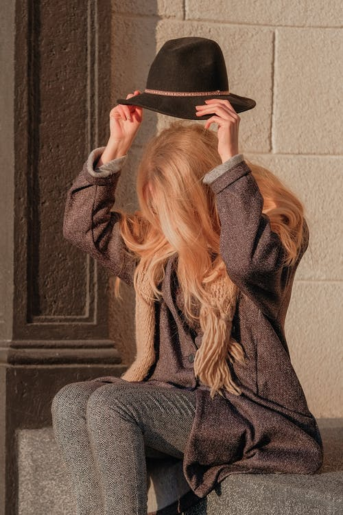 Woman in Gray Sweater Covering Her Face With Brown Scarf
