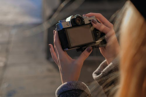 Woman shooting on old fashioned photo camera