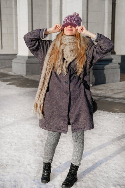 Full body of shy female in warm outerwear standing on snow and covering face with knitted hat