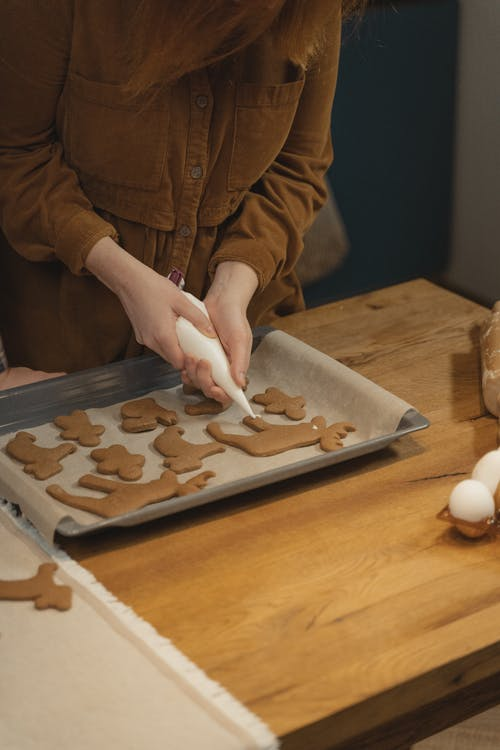 Person Frosting Brown Dough with Piping Bag