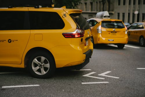 Yellow taxi cars riding along city street