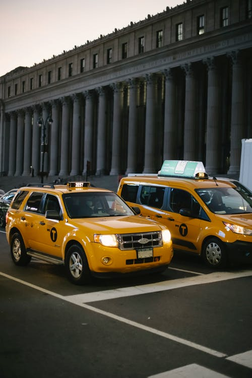 Stylish modern yellow SUV and minivan taxi cars with glowing headlights on city street near aged building with columns at sunset