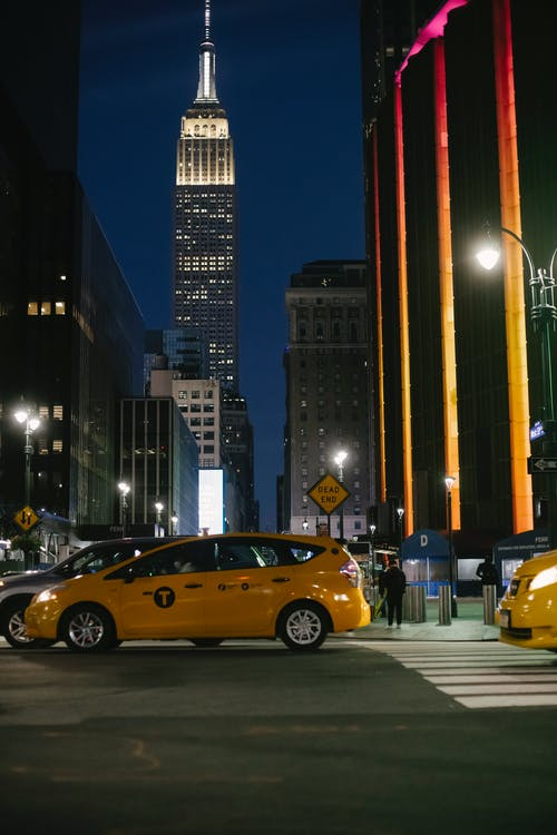 Contemporary cars riding on night city street near illuminated skyscrapers