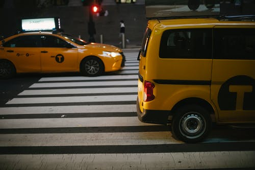 Various shiny yellow cabs driving on street in evening