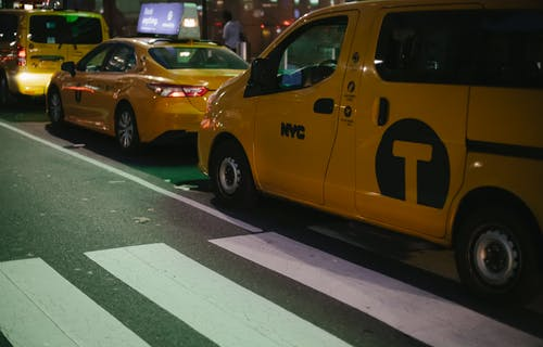 Modern various yellow taxi cars parked on street at night in New York City