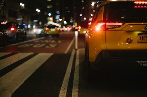 Stylish yellow SUV automobile driving on city street at night