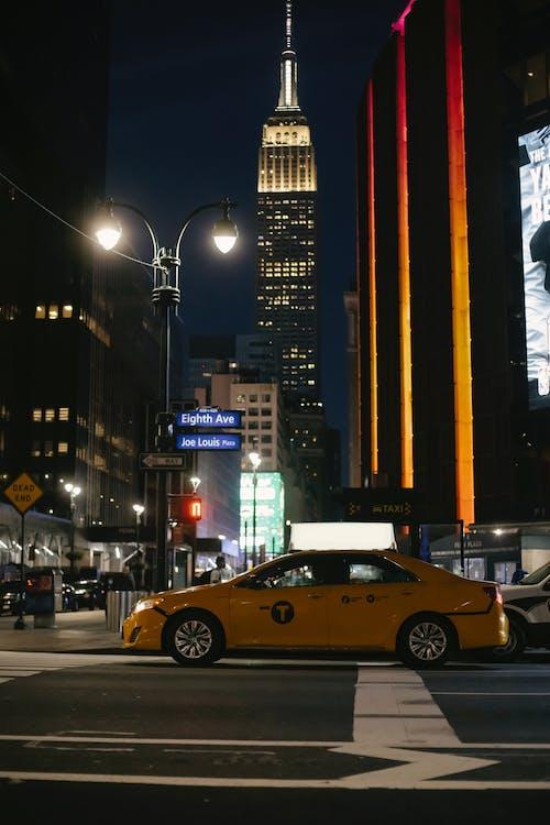 Contemporary yellow sedan taxi car stopped at zebra crossing near illuminated skyscraper in New York City at night