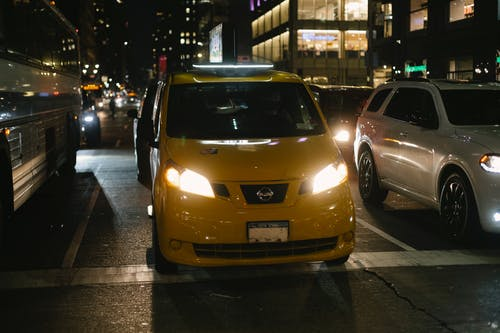 Shiny cab and automobiles driving on night city street