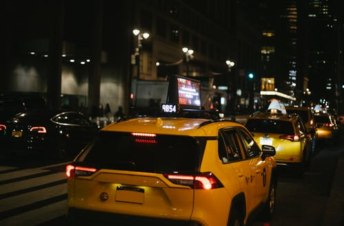 Hatchback taxis driving on city street at night