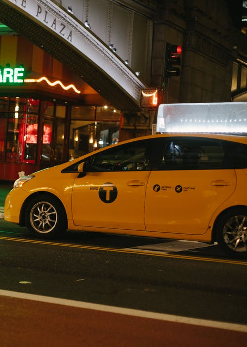 Minivan taxi car on city road near building with neon sign at night